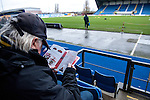 Oxford United 1 Accrington Stanley 2, 20/02/2016. Kassam Stadium, League Two. Oxford's home ground is the Kassam Stadium in Oxford and has a capacity of 12,500. United moved to the stadium in 2001 after leaving the Manor Ground, their home for 76 years. An Oxford supporter reads up on the visitors. Photo by Simon Gill.
