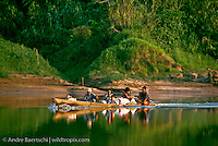 Ese Eja Indians travelling by motorized canoe on the lower Rio Tambopata, lowland tropical rainforest, Tambopata National Reserve, Madre de Dios, Peru.