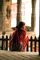 A Nepali woman rests on the steps of a temple in Durbar Square in Kathmandu. The literal meaning of Durbar Square is a place of palaces.