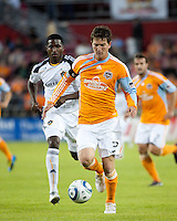 Bobby Boswell of the Houston Dynamo passes the ball away from Edson Buddle of the Los Angeles Galaxy get tangled up as they fight for the header during the regular season game between the Los Angeles Galaxy and the Houston Dynamo at Robertson Stadium in Houston, TX on April 10, 2010. Los Angeles 2, Houston 0.