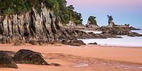 Coastal rock formations under pastel colours of twilight after sunset on Totaranui beach on Abel Tasman Coast Track, Abel Tasman National Park, Nelson Region, South Island, New Zealand
