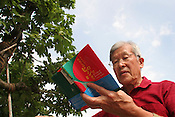 Yasuhiko Shigemoto, Japanese haiku poet, standing (with a book of his poetry) beside a tree which survived the August 6th 1945 atomic bombing of Hiroshima. The tree has been an inspiration for Mr. Shigemoto's poems, Hiroshima, Japan. 30.07.05