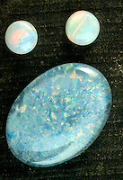 OPAL (CABOCHON CUT): INTERNAL IRIDESCENCE<br /> (Variations Available)<br /> Black Opal Doublet (large) with White Opals.SiO2.nH20<br /> Amorphous silicate with noncrystalline structure.  Electron microscopy shows structure to be regularly packed tiny spheres responsible for light interference creating the color play.
