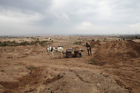 A man lifts a boulder onto his cart in the former Israeli settlement of Elei Sinai in Gaza's  northern buffer zone with Israel. The buffer zone is 300 meter wide stretch of land in which dozens have been maimed and killed by Israeli snipers.
