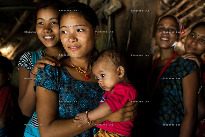 Villagers and 14 year old Tulasa Khadka's husband's extended family at home in the remote village of Dungi Khola, near Chhinchu, Surkhet district, Western Nepal, on 1st July 2012. Tulasa eloped at 13 and gave birth to a stillborn baby weighing less than 1 kg a week ago. She walks through the hills to the nearest hospital and she went into labour while on her way there for a checkup at almost full term. In Surkhet, Save the Children partners with Safer Society, a local NGO which advocates for child rights and against child marriage. Photo by Suzanne Lee for Save The Children UK