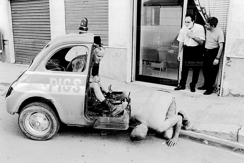 """Italy. Province of Sicily. Menfi. Mutoid Waste Company.  A man drives and tests the Fiat 250 (a Fiat 500 cuts in half) before the start of the show at """"Inycon"""" festival. Two other men look at the scene in front of a barber shop. One man has shaving cream on his face. Using all types of industrial scrap for their raw materials the Mutoid Waste Company are a mobile and adaptable group of performance artists. Having the necessary equipment to allow them complete freedom, they have created an entirely new form of scultural-musical performance crossing the boundaries of circus, theatre and art. © 1999 Didier Ruef"""