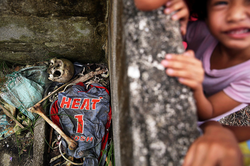 Children play in ruins above human remains and a basketball shirt found with it in the coastal part of Tacloban that was destroyed by Typhoon Haiyan January 16, 2015. Local residents said they found human remains in the mud among ruins of their wrecked fishing village and assume it is a typhoon victim. On his first visit to Asia's largest Catholic nation, Pope Francis will visit the central province of Leyte, which is still struggling to recover from Typhoon Haiyan that killed 6,300 people in 2013. About two million people are expected to attend an open-air mass on Saturday at Tacloban City airport, almost completely destroyed by Haiyan. REUTERS/Damir Sagolj (PHILIPPINES)