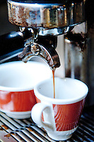 Espresso coffee being poured into cups at Tazza D' Oro, artisan coffee makers, Rome Italy