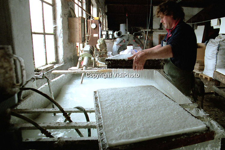 Foto: VidiPhoto..LOENEN - De oudste nog in bedrijf zijnde papierwatermolen van Nederland, De Middelste Molen in Loenen op de Veluwe (1622), moet uitbreiden. In de papiermolen wordt nog op de ouderwetse wijze de papierpulp met de hand geschept. Het resultaat is speciaal aquarelpapier. De lange vezels zorgen voor minder hobbels, waardoor het vrij kostbare eindproduct enorm populair is bij met name kunstenaars. Vooral de vraag vanuit met name Duitsland, Belgie en Frankrijk neemt flink toe. Foto: Eigenaar Piet Zegers schept de papierpulp in een grote zeef.