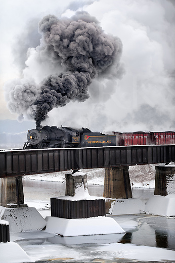 An old steam train in winter crossing bridge making a tall smoke plume rising in the cold air, with vintage freight cars following behind. It's leaving the West Virginia home yard and crossing into Maryland on the Western Maryland Scenic Railroad in Cumberland, Maryland.
