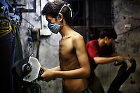 A textile worker wearing a face mask distresses a pair of jeans using a sanding machine at a garment factory. The factory, which specifically carries out a wear-and-tear process used to achieve a fashionable distressed look, produces approximately 10,000 pairs of jeans every day. Thousands of workers labour through the night scrubbing, spraying and tearing jeans in order to meet the production demand. The factory is owned by Huang Dehong, who left his impoverished village and arrived penniless in Zhongshan twenty years ago. China, the &quot;factory of the world&quot;, is now one of the world's largest producers of jeans and its textile workers are among the 200 million migrant labourers criss-crossing the country looking for a better life.