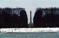 A stone column with a gold sculpture at its pinnacle overlooks the ornamental lake