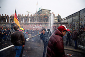 West Berlin, West Germany<br /> November 11, 1989<br /> <br /> East German police spray water on West Germans as they break through the wall at the Brandenburg Gate. The East German government lifts travel and emigration restrictions to the West on November 9, 1989.
