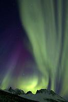 Aurora borealis swirls across the sky over the Brooks mountain range, Snowden mountain, arctic Alaska.