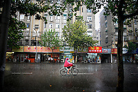 A bicyclist rides down a street during a late summer rainstorm in Nanjing, China.