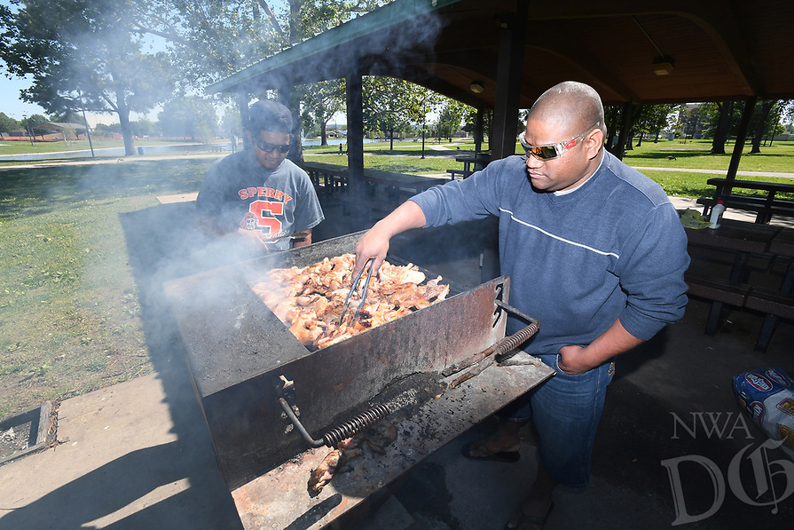 NWA Democrat-Gazette/J.T. WAMPLER Fredrick Jekkein, (right) and Marrel Jeik, both of Springdale, grill chicken Saturday May 13, 2017 at Murphy Park in Springdale. The men are originally from the Marshall Islands and were at the park to celebrate Mother's Day with family. The city will hold Murphy in May on Friday, May 19 to celebrate renovations to the park.