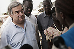 Antonio Guterres ecoute une responsable du HCR qui lui fait un point sur la situation au camp de Bahn au Liberia le 22 mars 2011<br />