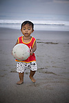 A young Balinese boy retrieves the football while playing early on Kuta beach in Bali.