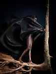 Woman in black outfit flying in the wind standing on a dried tree