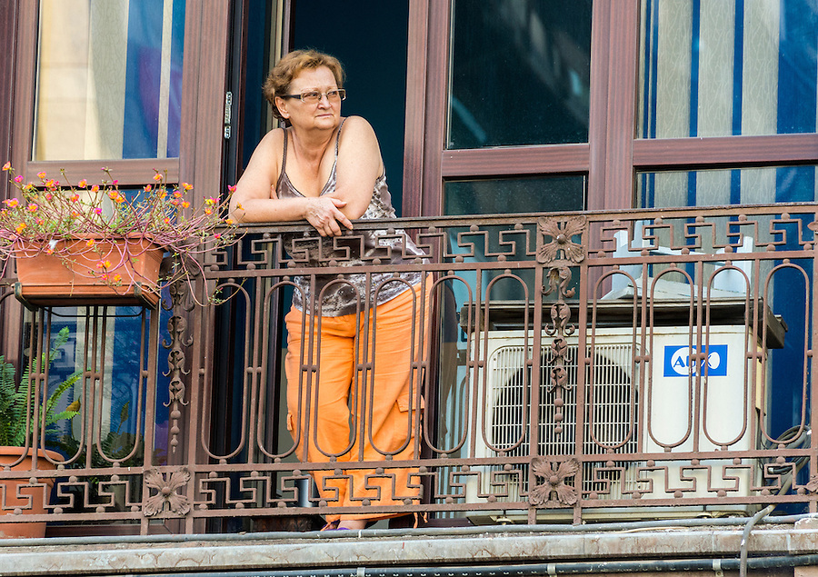 BUCHAREST, ROMANIA - September 29, 2012: Woman looking and relaxing in a balcony in Bucharest