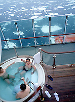 photograph by XAVIER CERVERA 06/2010.Three Chinese young men drinking beer and talking in the norwegian vessel MS Fram jacuzzi seventh floor meanwhile they can see melting ice in Greenland sea, next to Spitsbergen island, Svalbard archipielago
