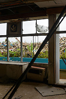 A derelict elementary school. The school clock was destroyed by the tsunami which reached the ceiling of the ground floor. Namie, Fukushima Prefecture, Japan, August 2, 2013. The town of Namie was evacuated following the nuclear accident of March 2011. Residents can only return for short periods to tend to their former homes and pick up belongings, and are not permitted to stay overnight.