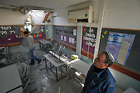 People inspect a classroom in a school after it was hit by a  Palestinian rocket. Israeli forces began an air offensive against Hamas in the Gaza Strip on 27/12/2008, which quickly escalated into an offensive by land, sea and air, in retaliation against Palestinian rockets fired into Israel. After eight days of bombardment, leaving over 400 Palestinians and four Israelis dead, Israeli tanks entered Gaza on 04/01/2009...