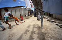 Honduran children displaced by Hurricane Mitch in 1998 play a game of hopscotch in the dirt alley of a settlement of temporary shelters in Tegucigalpa. The storm devastated the country leaving tens of thousands homeless.
