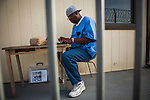 SAN QUENTIN, CA - APRIL 30, 2014: San Quentin News sportswriter Aaron Taylor writes outside their newsroom. CREDIT: Max Whittaker for The New York Times