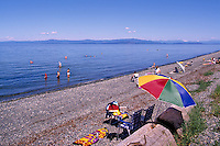 """People sunbathing on the Beach and wading and swimming in the Pacific Ocean at Qualicum Beach, in the """"Oceanside Region"""" of Vancouver Island, British Columbia, Canada"""