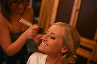 Bride has her makeup done before her wedding.