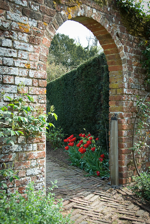 Brick archway into a walled garden, late April.