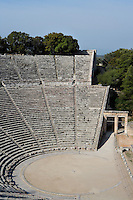 EPIDAURUS, GREECE - APRIL 15 : A view from the side of the Cavea and Orchestra of the Theatre, on April 15, 2007 in Epidaurus, Greece. The Theatre, designed by Polykleitos the Younger, was built in the late 4th century BC and extended in the Hellenistic period. It was rediscovered in 1881 and significantly restored in the 1950s.  It has the three main features of a Greek theatre: the orchestra, a sunken round stage; the skene, a raised rectangular stage beyond the orchestra; and the cavea, a raked semi-circular auditorium with radiating diazomas. To the right is the entrance to one of the two paradoi, or corridors, which gave the actors access to the stage. The theatre is renowned for its accoustics thanks to the symmetry of the cavea, seen here in the morning light. (Photo by Manuel Cohen)