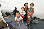 Abdul Fatah holds his three children as his wife Oruba Mousa looks on. They fled fighting in Daraa, Syria, and are sleeping in a tent in a camp for refugees on the Greek island of Chios. They crossed the Aegean Sea in a small boat from Turkey the previous day. They were registered and provided with food and shelter in a reception center built with support from International Orthodox Christian Charities, a member of the ACT Alliance. From Chios they will go to Athens and then on toward western Europe. Their goal is to get to Germany. Hundreds of thousands of refugees and migrants have passed through Greece in 2015.