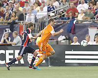 Houston Dynamo forward Cam Weaver (15) brings the ball forward as New England Revolution midfielder Scott Caldwell (6) closes. In a Major League Soccer (MLS) match, Houston Dynamo (orange) defeated the New England Revolution (blue), 2-1, at Gillette Stadium on July 13, 2013.