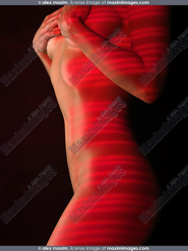 Nude woman body with red laser stripes on skin, isolated on black background. Skin resurfacing, rejuvenation artistic concept.