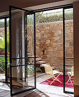 An open glass door leads out to a carpeted seating area on the terrace on one side of the house