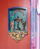 A carved crucifix with a painted angel and a miniature head of Buddha are displayed together in a turquoise-painted niche in the entrance hall