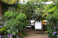 The outdoor dining area is in a secluded corner of the garden