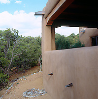 A detail showing the traditional building methods and materials used for the covered terrace of a contemporary adobe house in New Mexico
