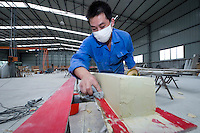 Worker molding a wind turbine blade, GHRE Power factory, Shanghai, China