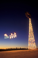 AJ5865, decorations, outdoor, Christmas, holiday, snow, winter, An illuminated Santa's sleigh pulled by reindeer flies through the air towards tall illuminated Christmas tree in East Montpelier at night in Washington County in the state of Vermont.