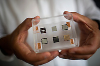 Paulo Lozano holds a case displaying the construction phases of small thruster made of silicon, gold, and porous metals that will be used in orbit on small satellites.  Lozano is the Associate Director of the Space Propulsion Lab and an Associate Professor of Aeronautics and Astronautics at MIT in Cambridge, Massachusetts, USA.  Lozano's current research focuses on the development of small thrusters for satellites.  The thrusters his lab has developed are about the size of a single die cube and contain enough fuel to power the thrusters for a year in space.  The thrusters will be used on small satellites.