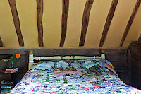 In the bedroom the yellow ochre ceiling contrasts with the dark wood of the walls and the patchwork quilt on the double bed