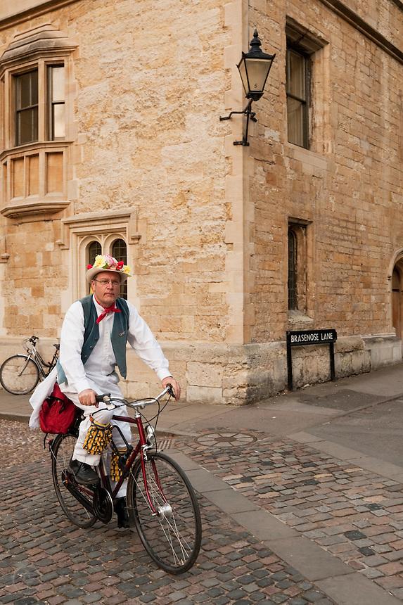A Morris dancer navigates Oxford's Brasenose Lane by bicycle on May Morning.
