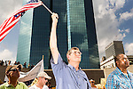 July 13, 2015. Winston Salem, North Carolina.<br />  John Chase, of Durham, NC, waves a flag to show his  support for the NC NAACP's lawsuit against Gov. Pat McCrory.<br />  To rally support for the North Carolina NAACP's case against Gov. Pat McCrory (NC NAACP v. McCrory), a march was held in downtown Winston Salem on the opening day of the case in federal court. Thousands gathered to walk the streets of downtown and listen to speeches proclaiming the importance of defeating new requirements for voter registration,<br />  The NC NAACP contests that HB 589 (Voter ID requirements) violate Section 2 of the Voting Rights Act (42 U.S.C. 1973) and the Fourteenth and Fifteenth Amendments of the Constitution.