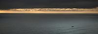 Fishing boat in Tasman Sea at sunset, West Coast, South Westland, New Zealand