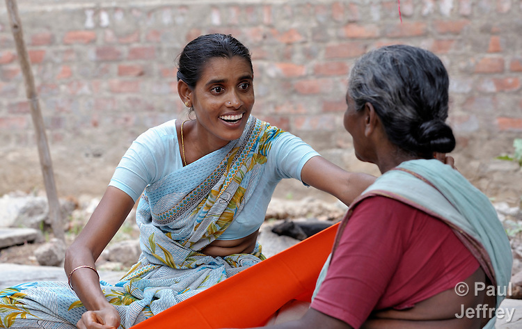 A. Kamala, an HIV positive widow in Guntur, Andhra Pradesh, India, supports herself and her children by selling sari cloth. Here she convinces a customer that it's the right color for her. (Note Special Instructions below.)
