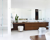 A stylish, spacious master bathroom features double washbasins on a bespoke cabinet.