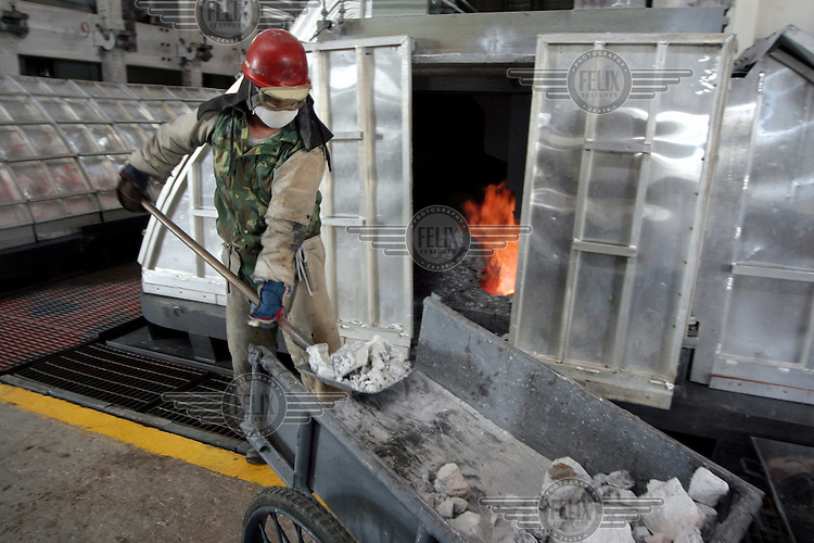 A worker shovels raw material into a smelter at an aluminium plant.